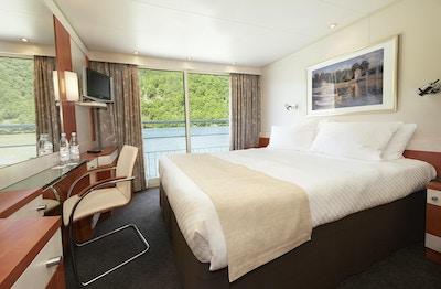 Stuga med dubbelsäng, bild på väggen, spegel, matta, stol, TV, stora fönster och fransk balkong