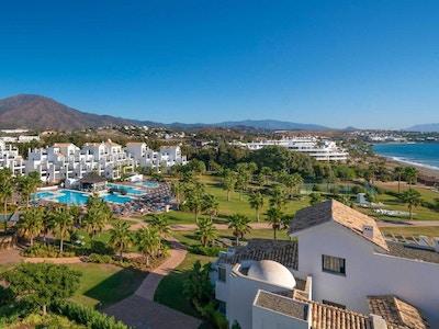 Hotellområdet med palmer, pool och strand, i bakgrunden syns Estepona centrum, Estepona Hotel & Spa Resort, Estepona, Spanien