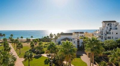 Härligt grönskande hotellområde med palmer och det glittrande Medelhavet i bakgrunden, Estepona Hotel & Spa Resort, Estepona, Spaien