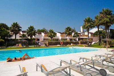 Pool med solsängar, palmer och hotellets lägenheter i bakgrunden, Hotel Encinar de Sotogrande, Estepona, Spain