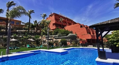 Pool med solstolar och palmer, hotellet och glå himmel, Manilva Green, Marbella, Spanien
