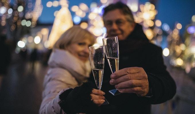 Stående av ett höga par i centrum på en kall vinterdag. De skålar med champagne och de ler. Vi kan se julbelysning bak.
