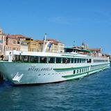 Kryssningsbåten MS Michelangelo ligger i solskenet i hamnen vid floden Po