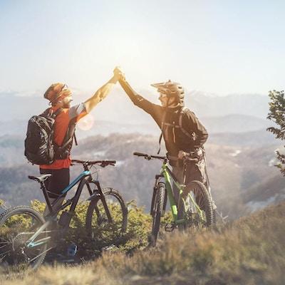 Två unga mans på ett berg, det var ride var fantastisk, kände sig glad och le med solen.