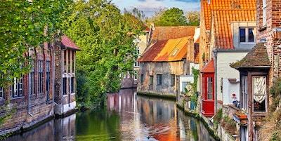 Brugge, Belgien. Medeltida forntida hus gjorda av gamla tegelstenar på vattenkanalen med båtar i gamla stan. Sommarsolnedgång med solsken och gröna träd. Pittoreska landskap.