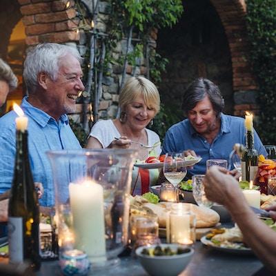 En grupp mogna vänner sitter runt ett matbord utomhus, äta och dricka.