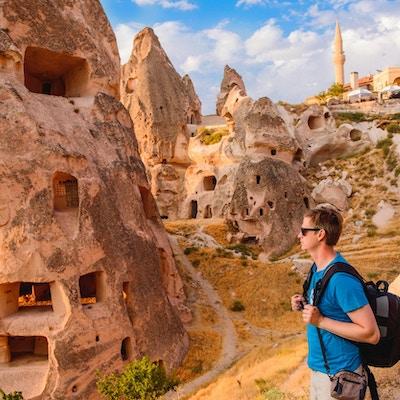 Turist som går längs grottan vaggar i Cappadocia, en historisk region i centrala Anatolien, Turkiet