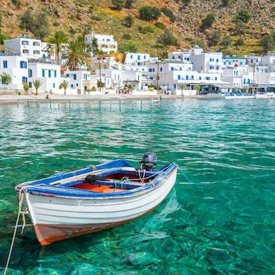 Fiskebåt och den natursköna byn Loutro på Kreta, Grekland