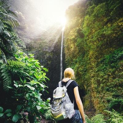Ung kvinna som tycker om vattenfallet Caldeiré Verde när hon vandrar på Madeira Island.
