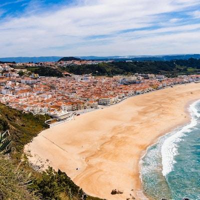 Underbar romantisk eftermiddag panoramautsikt över kusten i Atlanten. Se Nazare strandrivier, Praia da Nazare, med stadsbilden av Nazare stad under lågsäsong vid soligt väder. Portugal.