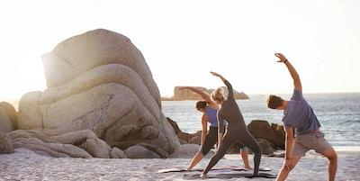 Skott av en grupp människor som övar yoga på stranden