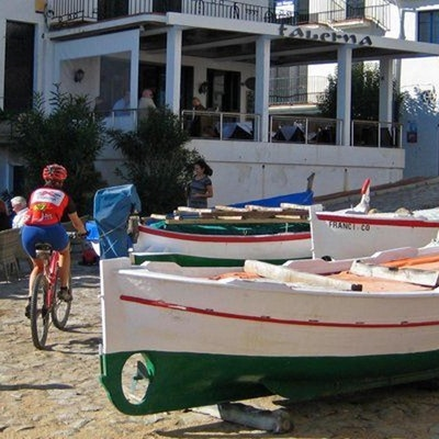 Cyklist passerar fiskebåtar. foto