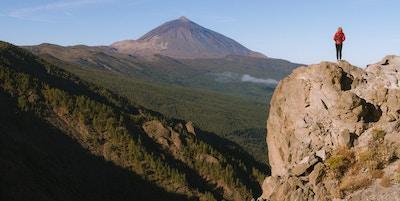 Kvinna i bergen som ser vulkanen