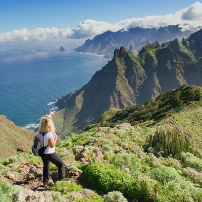 Kvinnafotvandrare som håller ögonen på härligt costal landskap. - Teneriffa, Kanarieöarna, Spanien. Västra kustvy, berg Anaga och Atlanten