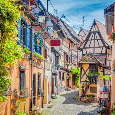 Charmig gatubildplats med färgglada hus i den historiska staden Eguisheim på en vacker solig dag med blå himmel och moln på sommaren, Alsace, Frankrike