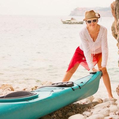 En kvinnlig kajakpaddlare som står på stranden vid Adriatiska havet i Dubrovnik