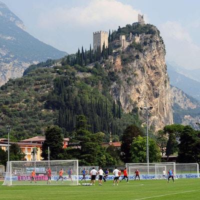 Proffslag tränar på konstgräsplan med berg i bakgrunden, Garda, Italien