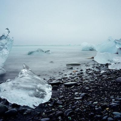Isberg på stranden vid Jökulsárlón glaciärlagun, södra Island