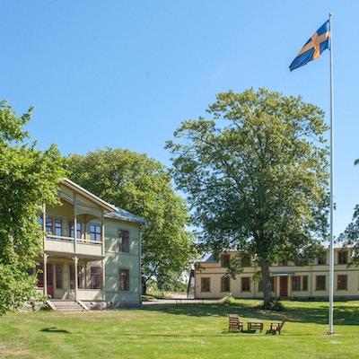 Logibyggnader, grönområde, träd, blå himmel, svensk flagga, Brunnsparken, Ronneby, Sverige