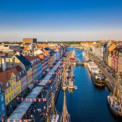 Stadskanal med segelfartyg, flankerade av gator med danska flaggor. Antenn.