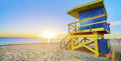 Miami South Beach soluppgång med badvaktstorn och kustlinje med färgglada moln och blå himmel.