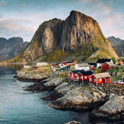 Norsk fiskeläge på Lofoten i Norge. Dramatiska solnedgångmoln som rör sig över branta bergstoppar