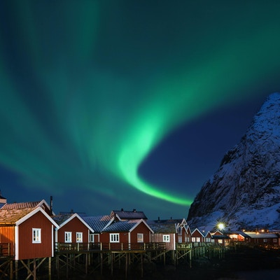 Härlig form av norrsken (Aurora borealis) över traditionella norska fiskestugor (rorbuer) och snöiga berg.