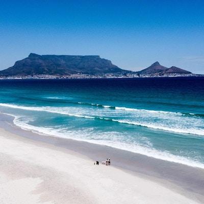 Vacker sandstrand en solig dag, underbar utsikt mot Kapstaden och Taffelberget, Sydafrika