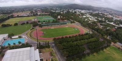 Foto från ovan över Coetzenburgs idrotssfaciliteter, utomhus 50-metersbassäng, friidrottstadion, naturgräsplaner, landhockeyplaner, tennisbanor, Stellenbosch, Sydafrika