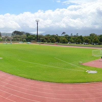 Friidrottstadion med kast- och hoppområden och en liten läktare, berg i bakgrunden, Coetzenburg Athletics Stadium, Stellenbosch, Sydafrika