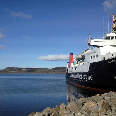 Färja från Caledonian MacBrayne vid Kennacraigs hamn i väntan på avresa till Islay, fin vårmorgon med blå himmel och lugnt hav, Skottland, Storbritannien