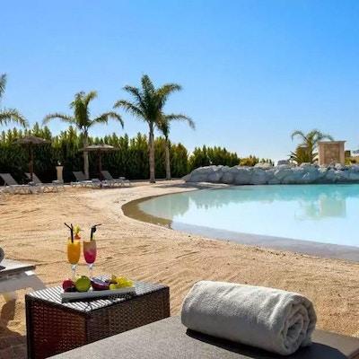Utomhus pool med konstgjord sandstrand, palmer, solstolar, blå himmel och sol, Melia Villaitana, Alicante, Spanien