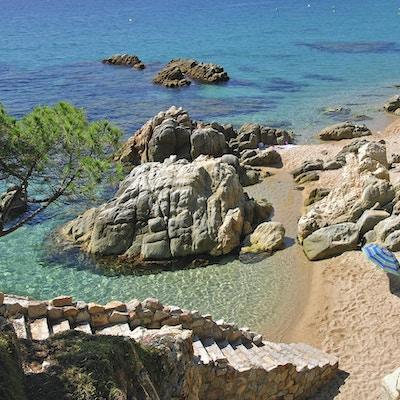 öde strand med parasoll och kristallklart vatten