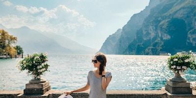 Ung härlig kvinna som kopplar av på den pittoreska Garda sjön. Semester koncept