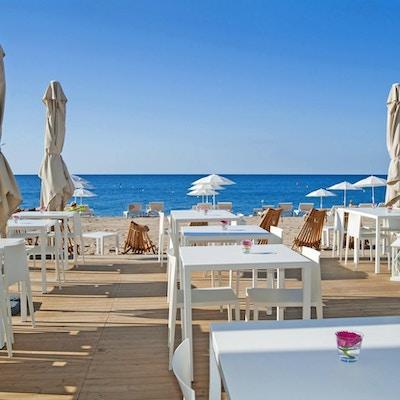 Beach club med trädäck, solstolar, parasoller, sandstrand, hav, blå himmel, Hotel Bernat II, Calella, Spain